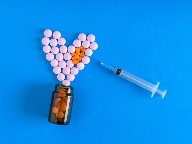 Die nadel der spritze ist auf das herz der pillen auf blauem grund gerichtet. der blick von oben. das konzept der behandlung und prävention von krankheiten. flach liegen.