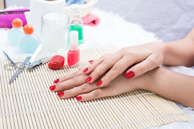 Die nägel der schönen manikürten frau mit rotem nagellack