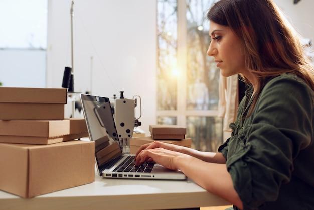 Die näherin arbeitet an neuen kleidungsstücken, die vom internet-kunden bestellt wurden