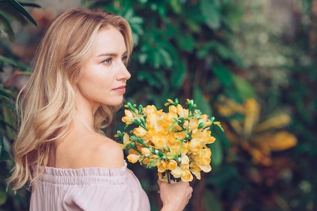 Die nahaufnahme der blonden jungen frau, die gelben blumenblumenstrauß in der hand hält