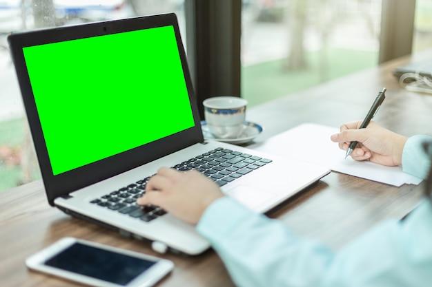 Die nahaufnahme der geschäftsfrau arbeitend mit laptop machen eine anmerkung in der kaffeestube wie dem hintergrund.
