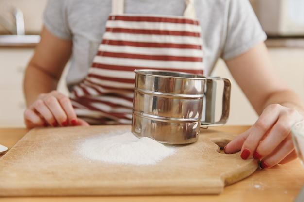 Die nahaufnahme der jungen frau in schürze mit eisensieb und mehl auf dem tisch in der küche. kochen nach hause. essen zubereiten.