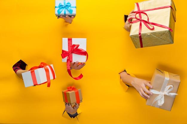 Die nahaufnahme der weiblichen hand, die ein geschenk durch ein zerrissenes gelbes papier hält, das verkaufs- und einkaufskonzept