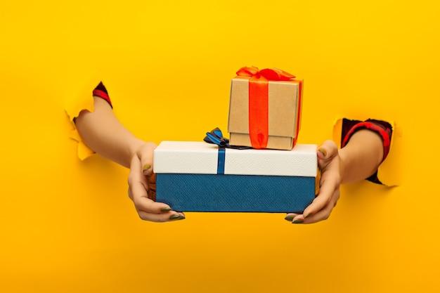 Die nahaufnahme der weiblichen hand, die ein geschenk durch ein zerrissenes gelbes papier hält, isoliert