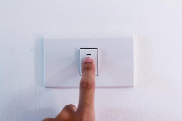 Die nahaufnahme des fingers schaltet den lichtschalter ein oder aus.
