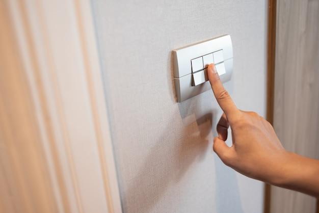 Die nahaufnahme des fingers wird im lichtschalter ein- oder ausgeschaltet.