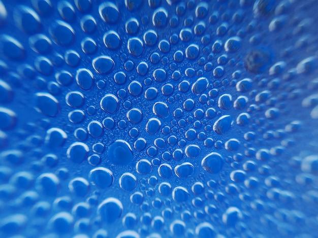Die nahaufnahme, die vom dampfwasser geschossen wird, fällt auf blauen hintergrund mit radialunschärfeeffekten