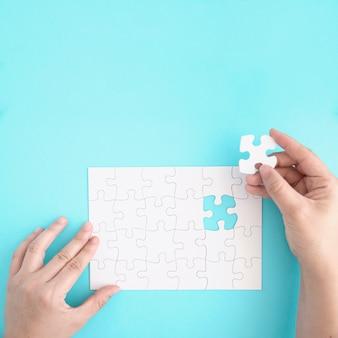Die nahaufnahme einer person, die das letzte stück hält, passt, um das puzzle zu vervollständigen