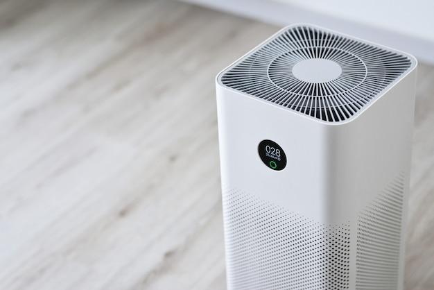 Die nahaufnahme eines innenluftreinigers im raum ist sehr sicher und sauber zu atmen, während die staubluftverschmutzungssituation draußen wirklich schlecht ist. schützen sie das pm 25-staub- und luftverschmutzungskonzept luftreiniger
