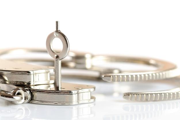 Die nahaufnahme eines schlüssels öffnet eine handschelle, die auf einem weißen tisch liegt. konzept entlassung aus der haft. freiheit von stereotypen und komplexen. platz für werbung