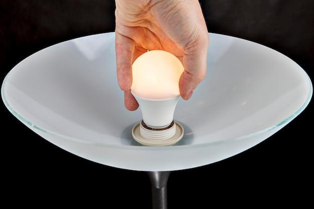 Die nahaufnahme ersetzt die glühbirne und dreht das led-licht in die fassung.