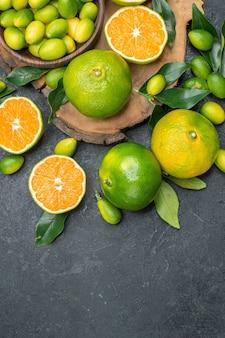 Die nahaufnahme von oben trägt früchte auf dem brett verschiedener arten von zitrusfrüchten auf dem dunklen tisch