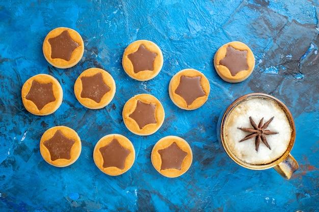 Die nahaufnahme von oben versüßt verschiedene kekse mit einer tasse kaffee