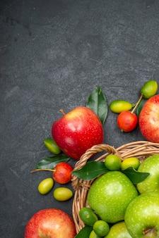 Die nahaufnahme zeigt den korb mit grünen äpfeln neben den zitrusfrüchten mit roten äpfeln, kirschen und früchten