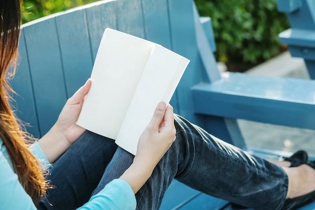 Die nahaufnahmefrau, die für das lesen eines buches in der freizeit im garten mit sonnenlicht entspannen sitzt herein sich zeit des asiatischen frauenkonzeptes