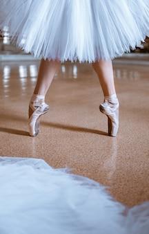 Die nahaufnahmefüße der jungen ballerina in spitzenschuhen
