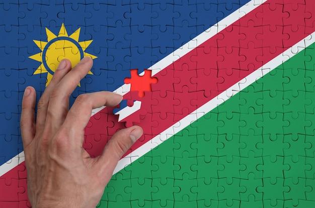 Die namibia-flagge ist auf einem puzzle abgebildet, das mit der hand des mannes gefaltet wird