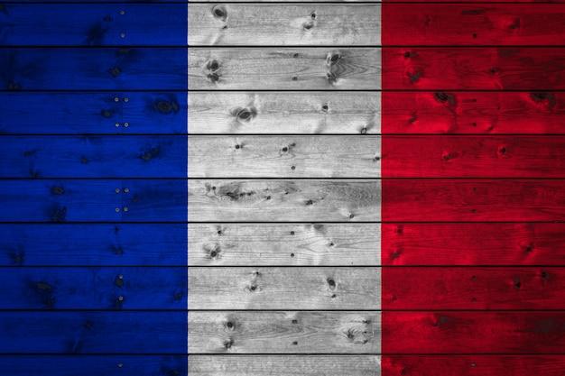 Die nationalflagge frankreichs ist auf ein lager mit geraden brettern gemalt, die mit einem nagel genagelt sind.
