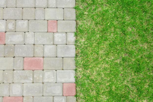 Die natürliche hintergrundstraße ist mit kopfsteinpflaster unter der rasenallee im hinterhof gepflastert