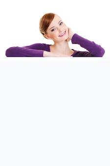 Die nett lächelnde erwachsene weibliche person ist über einer leeren werbetafel - auf einem weißen raum