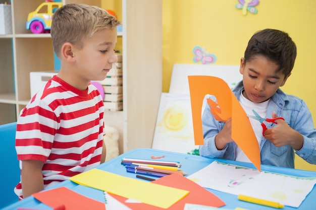 Die netten kleinen jungen, die papier schneiden, formt in klassenzimmer