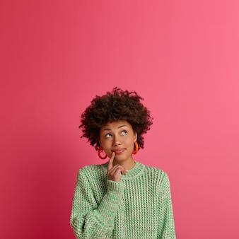 Die neugierige afroamerikanerin konzentriert sich oben, versucht etwas zu entscheiden, steht in nachdenklicher haltung, hält den finger in der nähe der lippen, trägt einen gestrickten pullover, isoliert an der rosa wand, leerzeichen nach oben