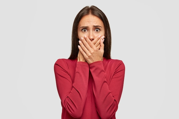 Die niedergeschlagene, verwirrte dame erfährt von einer tragödie mit einem freund, wird vor kummer weinen und hält beide hände auf dem mund