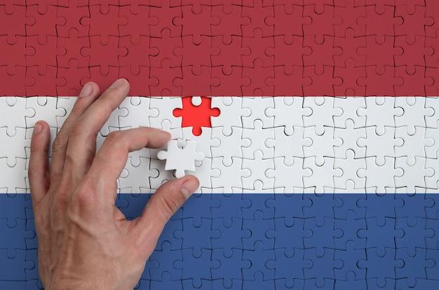 Die niederländische flagge ist auf einem puzzle abgebildet, das mit der hand des mannes gefaltet wird