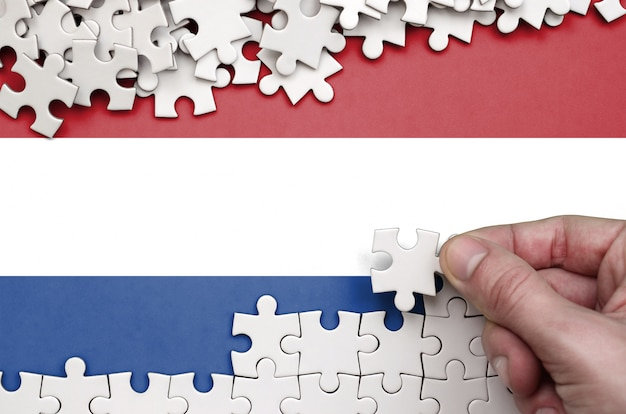 Die niederländische flagge ist auf einem tisch abgebildet, auf dem die menschliche hand ein puzzle weißer farbe faltet