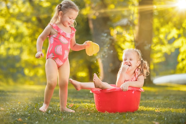 Die niedlichen kleinen blonden mädchen, die mit wasser spielen, spritzen im sommer auf dem feld