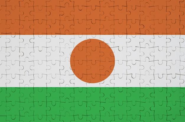 Die niger-flagge ist auf einem gefalteten puzzle abgebildet