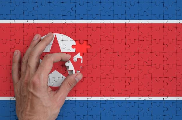 Die nordkorea-flagge ist auf einem puzzle abgebildet, das mit der hand des mannes gefaltet wird