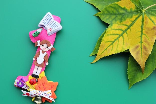 Die nummer eins besteht aus filz mit dem bild eines schulmädchens, eines schulhefts, eines bleistifts und ahornblättern.