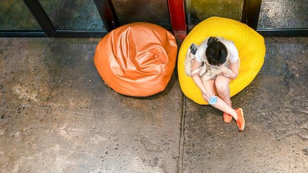 Die obere luftaufnahme der frau benutzt handy und sitzt auf gelbem sitzsack mit dem boden