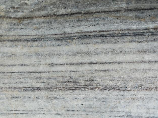 Die oberfläche des hellgrauen marmorsteinbeschaffenheitshintergrundes. mehr als eine million jahre alt