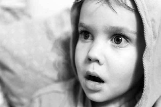 Die offenen emotionen der kinder im gesicht. porträt eines kleinen jungen mit einem überraschten oder verängstigten gesichtsausdruck. weit geöffnete augen und mund. schwarz-weiß getönt. laut und korneffekt