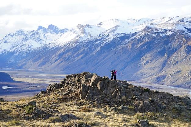 Die paarreisenden, die auf der bergspitze mit freude in patagonia, argentinien stehen.