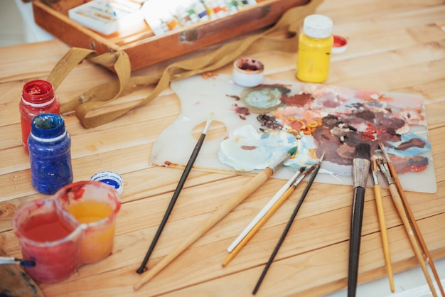 Die palette des künstlers. farbige ölfarben über eine palette auf einem tisch.
