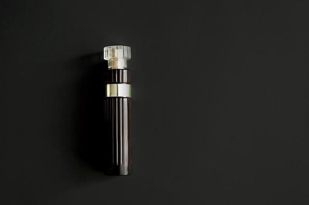 Die parfümflasche ist dunkelrot auf dunklem hintergrund. einer.