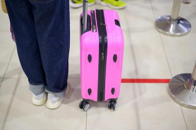 Die passagiere stehen am check-in-schalter in der schlange auf dem boden, um die soziale distanz aufgrund der sicherheitsrichtlinie für coronavirus-pandemien aufrechtzuerhalten