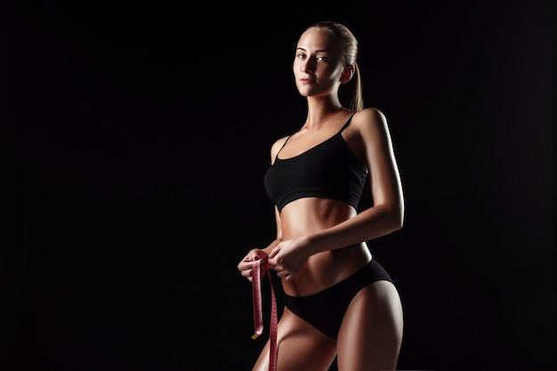 Die passende frau, die die perfekte form der schönen figur misst. gesunde lebensweise und fitnesskonzept