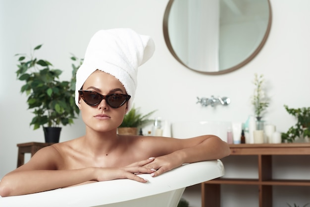 Die pathos schöne frau mit vitiligo liegt im bad in der sonnenbrille der katze und einem handtuch