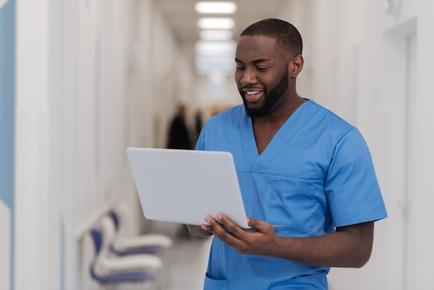 Die pause bei der arbeit genießen. erfahrener gutaussehender afroamerikanerpraktiker, der im krankenhaus steht, während er arbeitet und modernes gerät benutzt