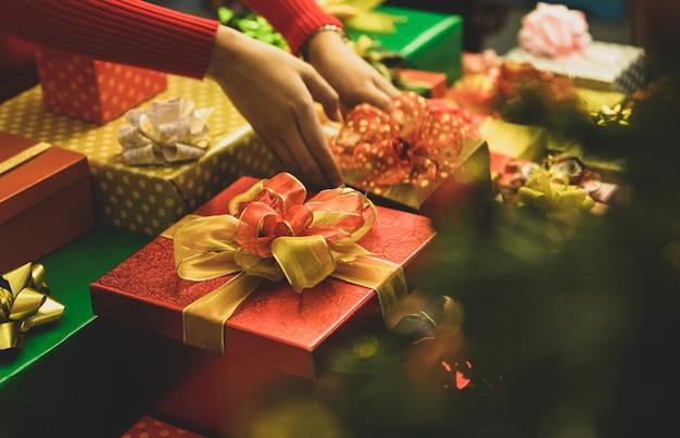 Die person auf dem pullover legte eine charmante geschenkbox mit einer wunderschönen bunten schleife auf den tisch, um ein schönes geschenk für die familienfeier der winterferienfeier zu dekorieren. fügen sie etwas rauschen hinzu, um das bild im vintage-stil anzupassen.