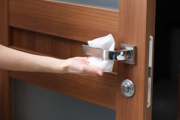 Die person desinfiziert und reinigt den türgriff mit antibakteriellen feuchttüchern, um sie vor viren, keimen und bakterien während des ausbruchs des coronavirus und der grippe-covid-ncov-epidemie zu schützen. sauberes zuhause