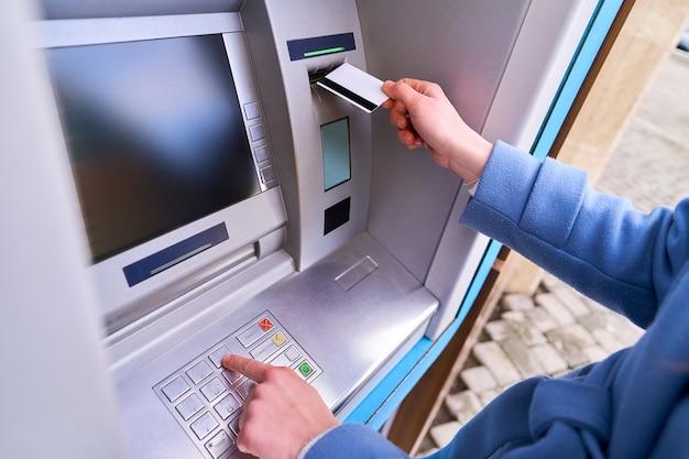 Die person legt eine plastikkreditkarte in die geldautomatenbank ein und wählt einen pin-code auf der tastatur, um geld abzuheben