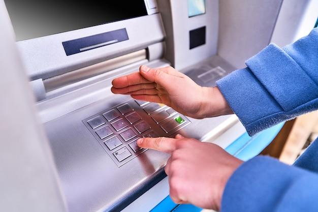 Die person wählt und versteckt mit anderen händen aus sicherheitsgründen einen pin-code auf der tastatur der geldautomatenbank, um bargeld abzuheben