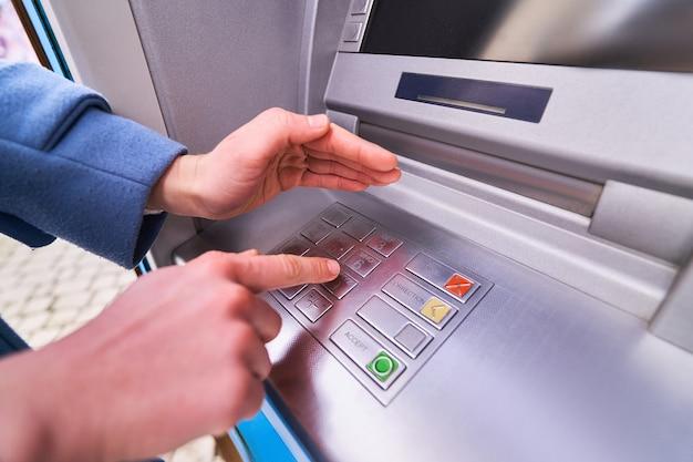 Die person wählt und versteckt mit anderen händen aus sicherheitsgründen einen pin-code auf der tastatur der geldautomatenbank, um geld abzuheben