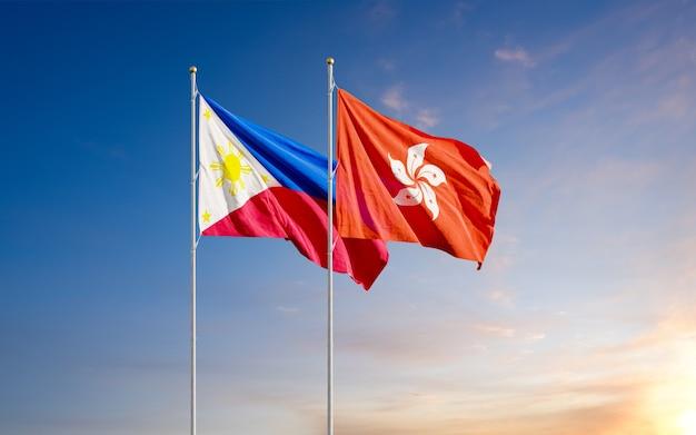 Die philippinischen und hongkonger flaggen fliegen zusammen im wind gegen den sonnenaufgangshimmel