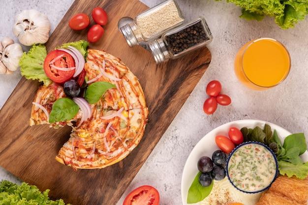Die pizza befindet sich in einem holztablett mit roten zwiebeln, schwarzen trauben, tomaten und salat.